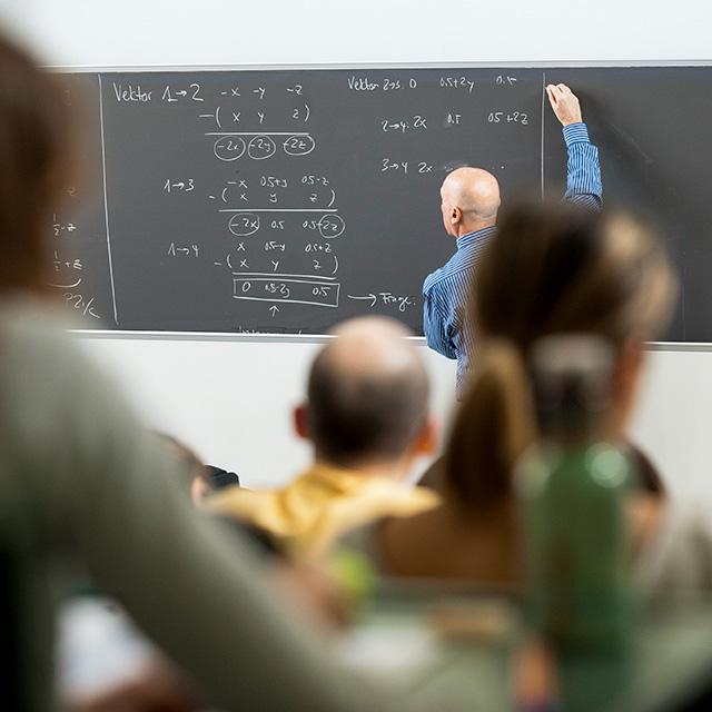 Professor schreibt Gleichungen auf eine Tafel, unscharf im Vordergrund Student*innen