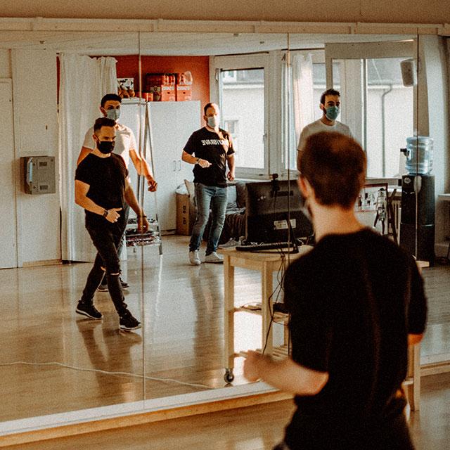 Männer in Spiegelung am Tanzen im Studio.