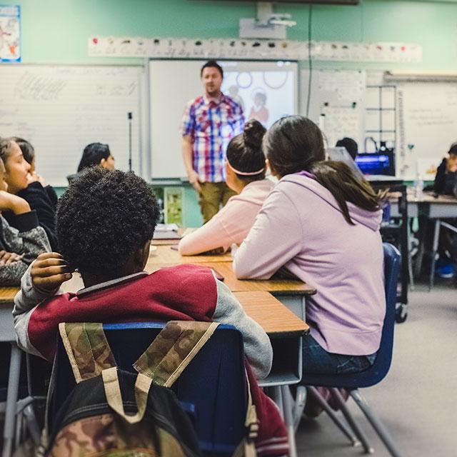 Bild aus Klassenzimmer mit Lehrer an Tafel